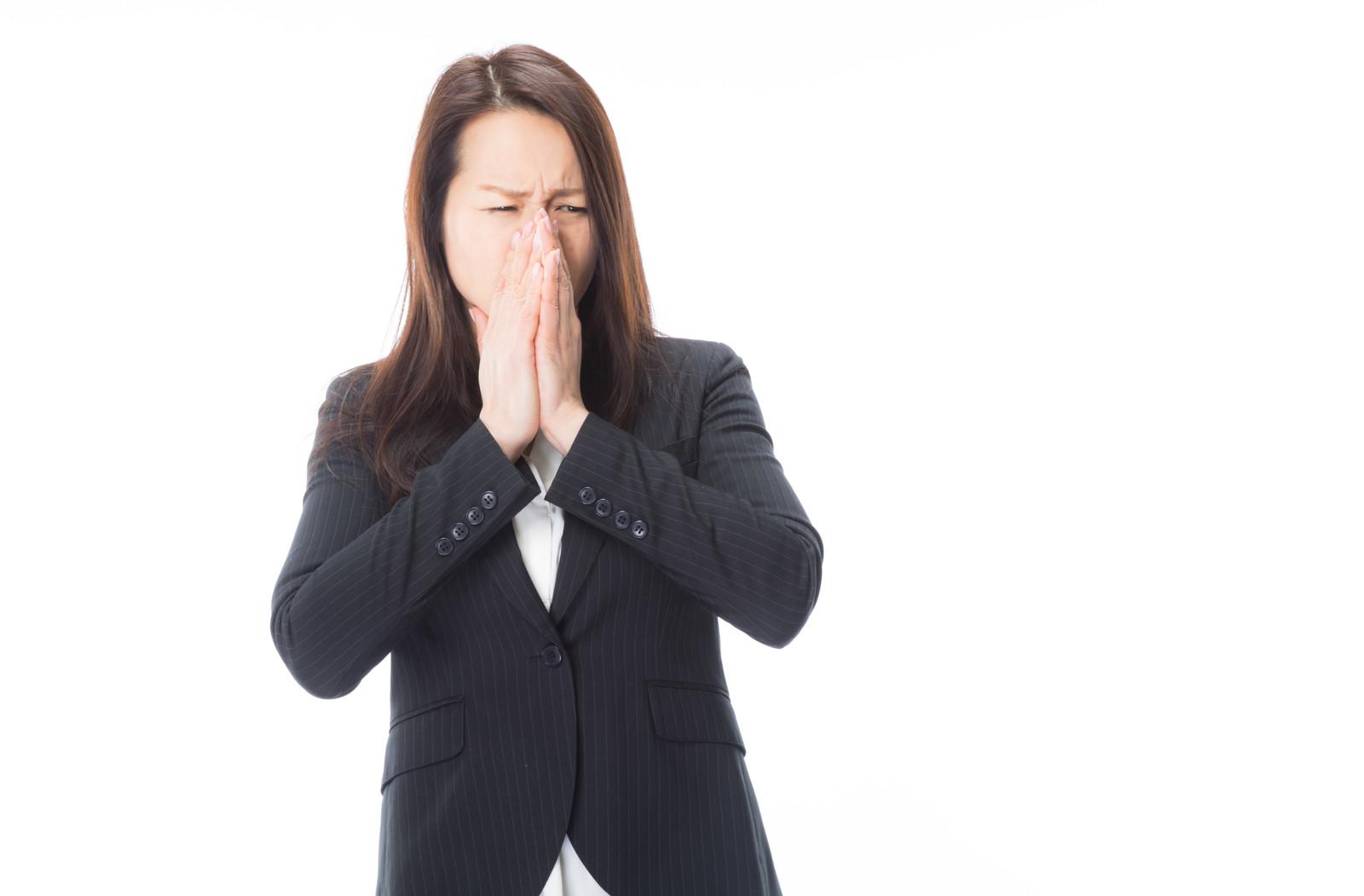 顔をしかめ鼻を覆う女性