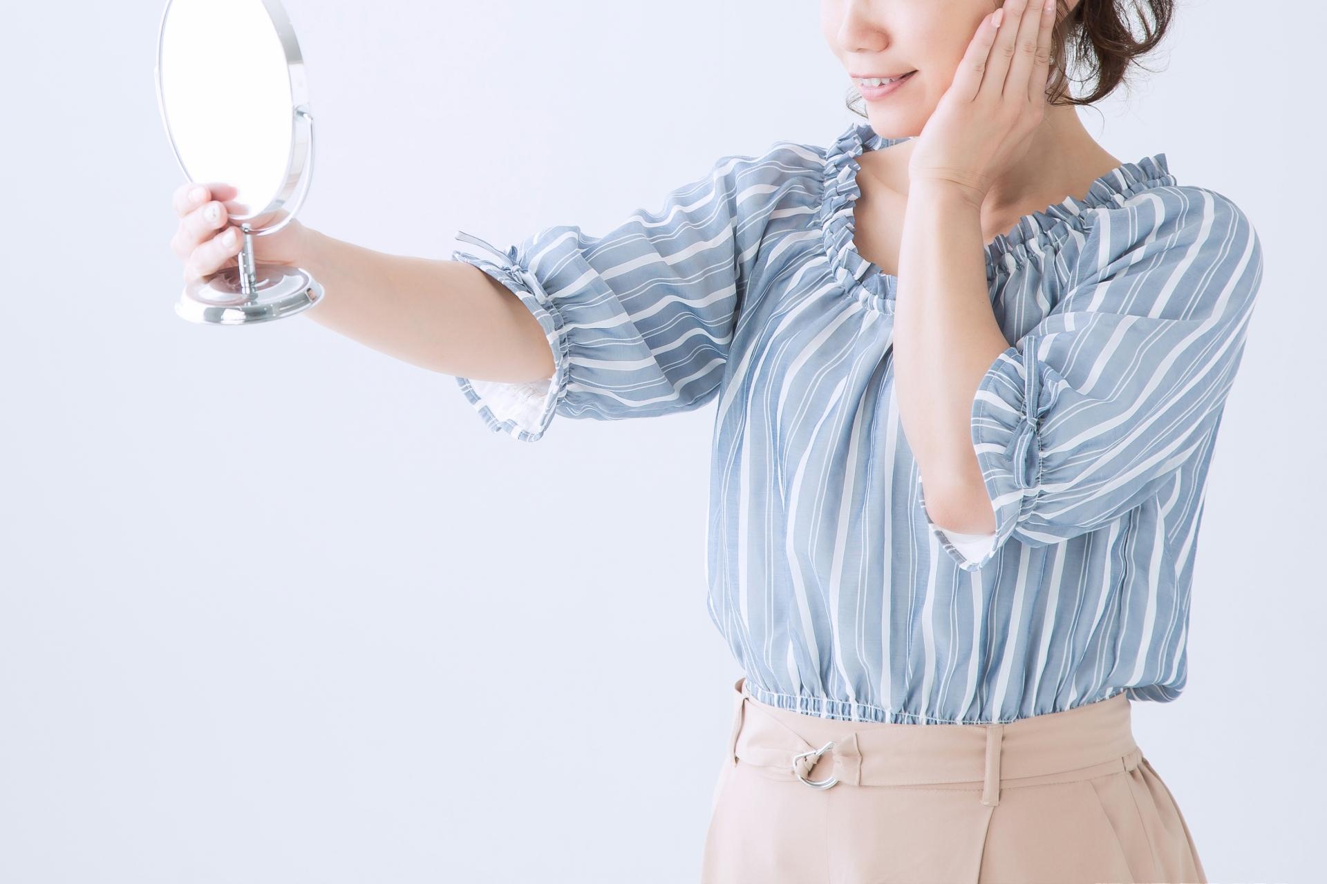 手鏡を見て実感する女性