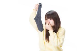 臭い靴下に鼻を摘む女性